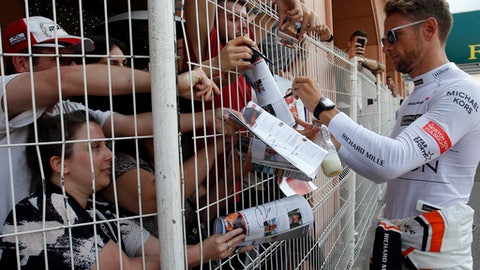 McLaren driver Jenson Button of Britain signs autographs after the second free practice during the Formula One Grand Prix at the Monaco racetrack in Monaco, Thursday, May 25, 2017. The Formula one race will be held on Sunday. (AP Photo/Claude Paris)