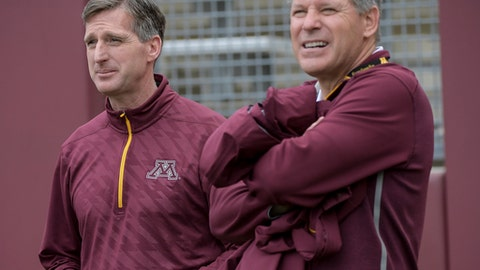 In this April 15, 2017 photo, University of Minnesota athletics fundraiser Randy Handel, right, and athletic director Mark Coyle watch from the sidelines during the Gophers' spring NCAA college football game at TCF Bank Stadium in Minneapolis. Handal, accused of sexual harassment, will be suspended without pay for two weeks and demoted.  The university on Thursday, May 25, 2017, released findings of an internal investigation of Handel, after a female subordinate said he repeatedly hugged, touched and made inappropriate comments to her.  Handel maintained he had no sexual intent toward the subordinate. (Aaron Lavinsky/Star Tribune via AP)
