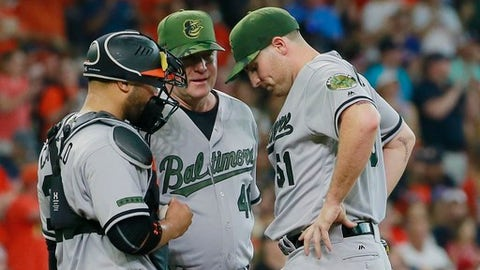 Baltimore Orioles' pitcher Alec Asher, right, reacts during the Houston Astros' six-run second inning as he conferences with catcher Welington Castillo, left, and pitching coach Roger McDowell during a baseball game Sunday, May 28, 2017, in Houston. (AP Photo/Richard Carson)