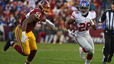 Jan 1, 2017; Landover, MD, USA; New York Giants running back Paul Perkins (28) rushes the ball as Washington Redskins linebacker Preston Smith (94) looks on during the first half at FedEx Field. Mandatory Credit: Brad Mills-USA TODAY Sports