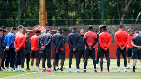 Manchester United's Wayne Rooney, center facing, stands alongside his teammates ahead of a training session at the AON Training Complex in Carrington, England, Tuesday May 23, 2017, for a minute of silence to remember the victims after an apparent suicide bomber attacked an Ariana Grande concert on Monday night. (Martin Rickett/PA via AP)
