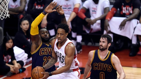 Toronto Raptors guard DeMar DeRozan (10) handles the ball in front of Cleveland Cavaliers forwards LeBron James (23) and Kevin Love (0) the first half of Game 4 of a second-round NBA basketball playoff series in Toronto, Sunday, May 7, 2017. (Nathan Denette/The Canadian Press via AP)