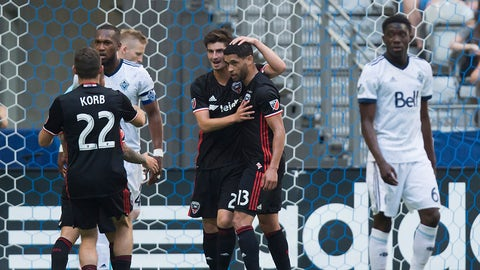 D.C. United's Lamar Neagle (13) celebrates his penalty kick goal with Ian Harkes and Chris Korb (22) as Vancouver Whitecaps' Kendall Wastonm back left, and Alphonso Davies, right, look on during the second half of an MLS soccer game in Vancouver, British Columbia, Saturday, May 27, 2017. (Darryl Dyck/The Canadian Press via AP)