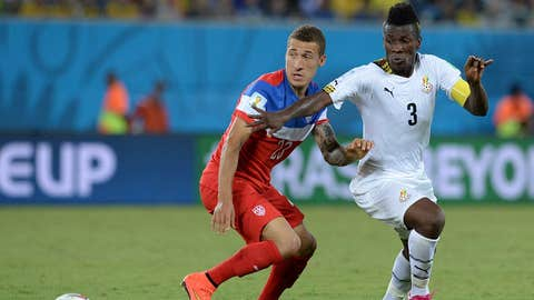 US defender Fabian Johnson (L) vies with Ghana's forward Asamoah Gyan (R) during a Group G football match between Ghana and US at the Dunas Arena in Natal during the 2014 FIFA World Cup on June 16, 2014.  AFP PHOTO / CARL DE SOUZA        (Photo credit should read CARL DE SOUZA/AFP/Getty Images)