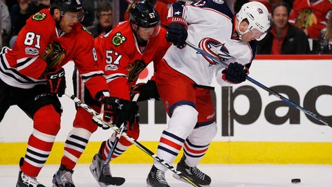 Columbus Blue Jackets left wing Scott Hartnell, right, controls the puck against Chicago Blackhawks right wing Marian Hossa, left, and defenseman Trevor van Riemsdyk during the first period of an NHL hockey game Friday, March 31, 2017, in Chicago. (AP Photo/Nam Y. Huh)