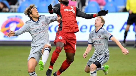 Toronto FC forward Jozy Altidore (17) brings down the ball as Chicago Fire defender Patrick Doody (22) and midfielder Dax McCarty (6) move in during the first half of an MLS soccer match in Toronto on Friday, April 21, 2017. (Frank Gunn/The Canadian Press via AP)
