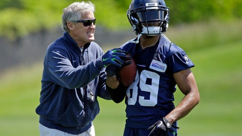 Seattle Seahawks head coach Pete Carroll, left, playfully grabs at the hands of wide receiver Doug Baldwin during NFL football practice, Friday, June 2, 2017, in Renton, Wash. (AP Photo/Ted S. Warren)
