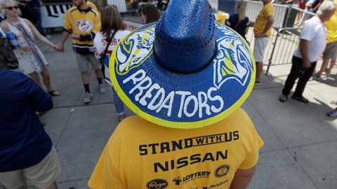 A Nashville Predators fan walks outside the arena before Game 3 of the NHL hockey Stanley Cup Finals between the Nashville Predators and the Pittsburgh Penguins Saturday, June 3, 2017, in Nashville, Tenn. (AP Photo/Mark Humphrey)
