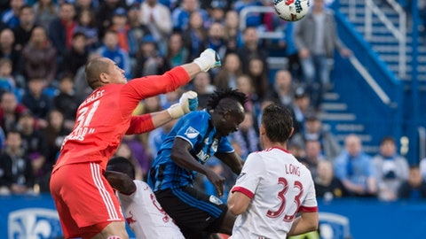 New York Red Bulls goalkeeper Luis Robles punches the ball away from Montreal Impact forward Dominic Oduro during the first half of an MLS soccer match Saturday, June 3, 2017, in Montreal. (Paul Chiasson/The Canadian Press via AP)