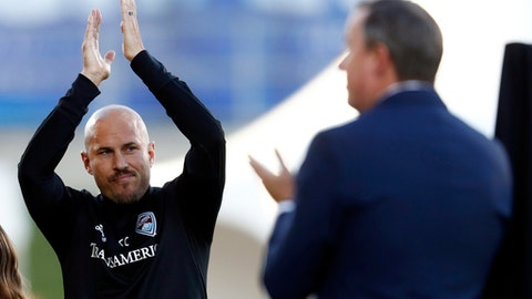 Conor Casey, left, applauds as he is inducted into the Colorado Rapids' gallery of honor for his years of play with the team during a ceremony before hosting the Columbus Crew in the first half of an MLS soccer game Saturday, June 3, 2017, in Commerce City, Colo. (AP Photo/David Zalubowski)