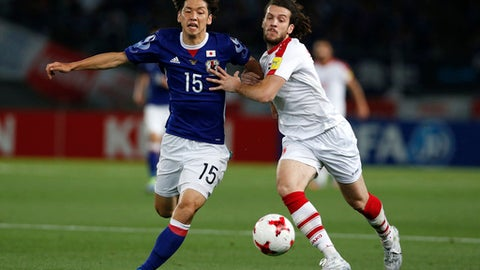 Japan's Yuya Osako, left, and Syria's Omro Al Midani vie for the ball during their Kirin Challenge Cup international friendly soccer match in Tokyo, Wednesday, June 7, 2017.(AP Photo/Shuji Kajiyama)