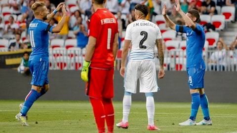 Italy's Andrea Belotti, right, celebrates with his teammate Ciro Immobile after Uruguay's Jose Gimenez, second from right, scored an own goal, during a friendly soccer match between Italy and Uruguay, at the Nice Allianz Riviera stadium, France, Wednesday, June 7, 2017. (AP Photo/Claude Paris)