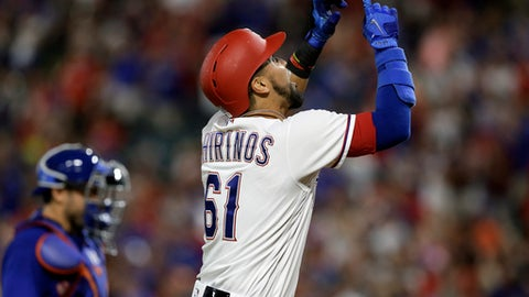 Texas Rangers' Robinson Chirinos (61) points skyward, celebrating his two-run home run, as New York Mets catcher Travis d'Arnaud walks back to the plate during the eighth inning of a baseball game, Wednesday, June 7, 2017, in Arlington, Texas. (AP Photo/Tony Gutierrez)