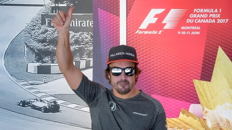 McLaren driver Fernando Alonso, of Spain, salutes the crowd as he arrives for an autograph session at the F1 Canadian Grand Prix auto race, Thursday, June 8, 2017, in Montreal. (Paul Chiasson/The Canadian Press via AP)