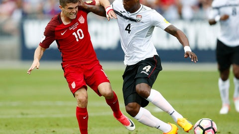 U.S. midfielder Christian Pulisic, left, passes the ball as Trinidad & Tobago defender Sheldon Bateau defends during the first half of a World Cup soccer qualifying match Thursday, June 8, 2017, in Commerce City, Colo. (AP Photo/David Zalubowski)