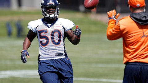 File--In this Monday, June 5, 2017, file photograph, Denver Broncos inside linebacker Zaire Anderson, left, tosses the ball to a coach during the team's NFL football minicamp session in Englewood, Colo. Anderson is happy to be back on the gridiron after he was knocked unconscious while covering a punt against the Oakland Raiders and then carted off the field. (AP Photo/David Zalubowski, file)