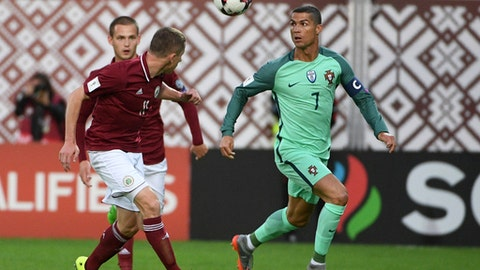 Latvia's Aleksandrs Solovjovs, left, and Portugal's Cristiano Ronaldo, right, fight for the ball during their World Cup Group B qualifying match between Latvia and Portugal at the Skonto Stadium in Riga, Latvia, Friday, June 9, 2017. (AP Photo/Roman Koksarov)