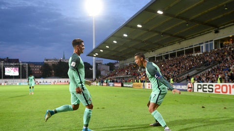 Portugal's Cristiano Ronaldo, right, reacts with Andre Silva, left, after scoring during World Cup Group B qualifying match between Latvia and Portugal at the Skonto Stadium in Riga, Latvia, Friday, June 9, 2017. (AP Photo/Roman Koksarov)
