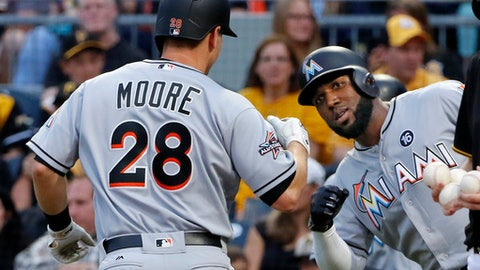 Miami Marlins' Tyler Moore (28) is greeted by Marcell Ozuna, who was on base for his two-run home run off Pittsburgh Pirates starting pitcher Tyler Glasnow during the third inning of a baseball game in Pittsburgh, Friday, June 9, 2017. (AP Photo/Gene J. Puskar)