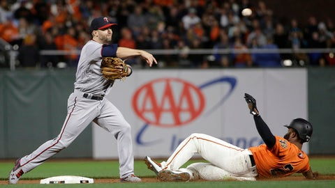 Minnesota Twins' Brian Dozier, left, throws to first base after forcing out San Francisco Giants' Denard Span at second base during the sixth inning of a baseball game in San Francisco, Friday, June 9, 2017. Eduardo Nunez was safe at first. (AP Photo/Jeff Chiu)