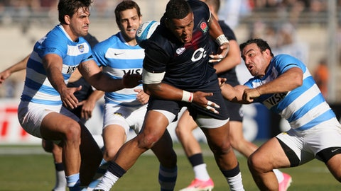 England's Nathan Hughes, center, is tackle by Argentina's Agustin Creevy, right, during a rugby test match in San Juan, Argentina, Saturday, June 10, 2017. (AP Photo/Emmanuel Rodriguez Villegas)
