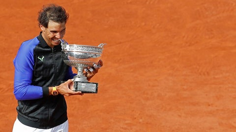 Spain's Rafael Nadal bites the trophy as he celebrates winning his tenth French Open title against Switzerland's Stan Wawrinka in three sets, 6-2, 6-3, 6-1, during their men's final match of the French Open tennis tournament at the Roland Garros stadium, in Paris, France, Sunday, June 11, 2017. (AP Photo/Petr David Josek)