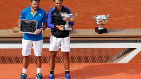 Spain's Rafael Nadal, right, holds the trophy as he celebrates winning his tenth French Open title against Switzerland's Stan Wawrinka, left, in three sets, 6-2, 6-3, 6-1, during their men's final match of the French Open tennis tournament at the Roland Garros stadium, in Paris, France, Sunday, June 11, 2017. (AP Photo/Petr David Josek)