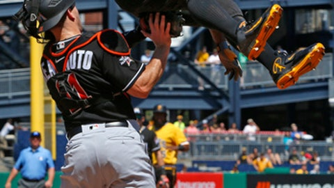 Pittsburgh Pirates' Andrew McCutchen, top, is tagged out by Miami Marlins catcher J.T. Realmuto as he attempts to score on a ground out by Pirates' John Jaso in the sixth inning of a baseball game in Pittsburgh, Sunday, June 11, 2017. (AP Photo/Gene J. Puskar)