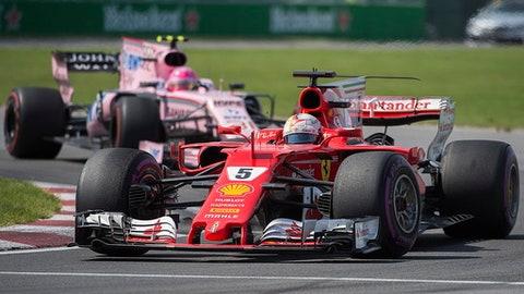 Ferrari driver Sebastian Vettel, of Germany, takes a turn at the Senna corner ahead of Force India driver Esteban Ocon, of France, at the Canadian Grand Prix auto race Sunday, June 11, 2017, in Montreal. (Graham Hughes/The Canadian Press via AP)