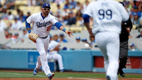 Los Angeles Dodgers first baseman Adrian Gonzalez, left, tosses the ball to starting pitcher Hyun-Jin Ryu, right, to get Cincinnati Reds' Joey Votto out during the first inning of a baseball game, Sunday, June 11, 2017, in Los Angeles. (AP Photo/Ryan Kang)