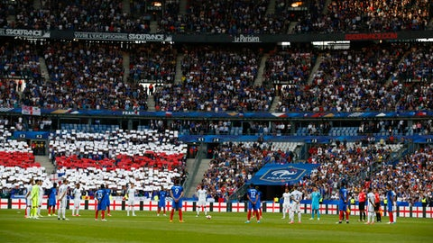 English and French players stand together during a minute of silence for the victims of the recent attacks in Manchester and London before a friendly soccer match between France and England at the Stade de France in Saint Denis, north of Paris, France, Tuesday, June 13, 2017. After their talks at the Elysee Palace, French President Emmanuel Macron and Britain's Prime Minister Theresa May watch a France-England football match that will honor victims of extremist attacks in both countries. (AP Photo/Francois Mori)