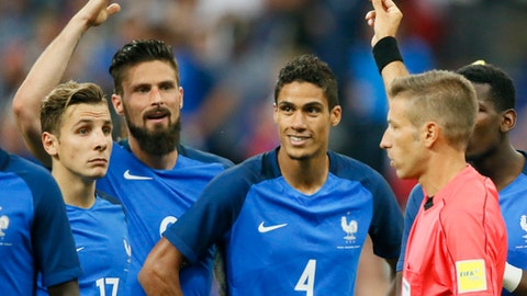 France's Raphael Varane, second right, gets the red card from referee Davide Massa during a friendly soccer match between France and England at the Stade de France in Saint Denis, north of Paris, France, Tuesday, June 13, 2017. (AP Photo/Francois Mori)