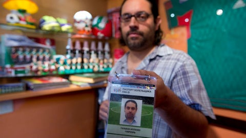 "In this May 24, 2017 photo, Gabriel Galvan, one of the founders of ""La Ola Verde,"" or the Green Wave, poses with his accreditation for the Confederations Cup soccer game between Mexico and Russia, at his home in Mexico City. From New Zealand to Ohio, a group of Mexican fans has been traveling the world for almost a decade following the national team. Its next stop is Russia, where ""El Tri"" plays in the Confederations Cup, a World Cup warmup tournament that starts Saturday. (AP Photo/Eduardo Verdugo)"