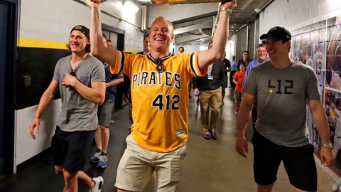 Pittsburgh Penguins' Patric Hornqvist hoists the Stanley Cup as he arrives with teammates Carl Hagelin, left, and Sidney Crosby, right, at PNC Park before a baseball game between the Pittsburgh Pirates and Colorado Rockies in Pittsburgh, Tuesday, June 13, 2017. (AP Photo/Gene J. Puskar)