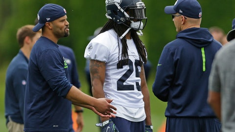 Seattle Seahawks cornerback Richard Sherman (25) talks with offensive coordinator Darrell Bevell, right, and defensive coordinator Kris Richard, left, during NFL football practice, Tuesday, June 13, 2017, in Renton, Wash. (AP Photo/Ted S. Warren)