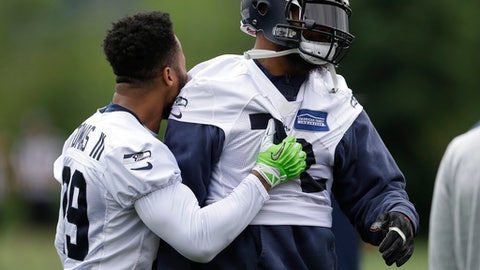 RETRANSMISSION TO CORRECT DATE -Seattle Seahawks defensive end Michael Bennett, right, reacts with free safety Earl Thomas, left, after Bennett fell while taking part in a drill during NFL football practice, Tuesday, June 13, 2017, in Renton, Wash. (AP Photo/Ted S. Warren)
