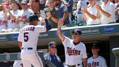 Fans cheer as Minnesota Twins manager Paul Molitor, right, high-fives Eduardo Escobar following Escobar's two-run home run off Seattle Mariners starting pitcher Ariel Miranda in the first inning of a baseball game Thursday, June 15, 2017, in Minneapolis. (AP Photo/Jim Mone)