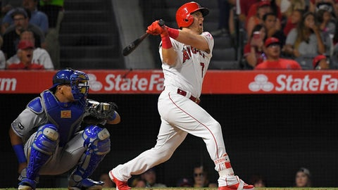 Los Angeles Angels' Cliff Pennington watches a solo home run in front of Kansas City Royals catcher Salvador Perez during the sixth inning of a baseball game, Friday, June 16, 2017, in Anaheim, Calif. (AP Photo/Mark J. Terrill)
