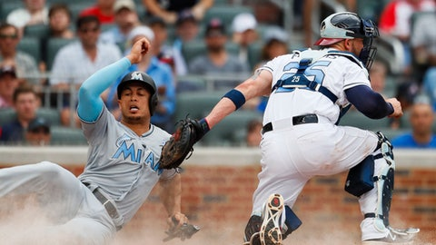 Miami Marlins Giancarlo Stanton (27) slides under the tag of Atlanta Braves catcher Tyler Flowers (25) to score in the fifth inning of a baseball game, Saturday, June 17, 2017, in Atlanta. (AP Photo/Todd Kirkland)
