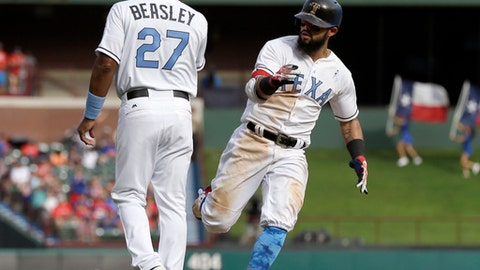 Texas Rangers third base coach Tony Beasley (27) congratulates Rougned Odor, right, on his solo home run that came off a pitch from Seattle Mariners relief pitcher Dan Altavilla in the sixth inning of a baseball game, Saturday, June 17, 2017, in Arlington, Texas. (AP Photo/Tony Gutierrez)