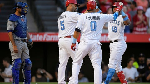 Los Angeles Angels' Luis Valbuena, right, is congratulated by Albert Pujols, second from left, and Yunel Escobar, second from right, after hitting a three-run home run as Kansas City Royals catcher Drew Butera, left, watches during the seventh inning of a baseball game, Saturday, June 17, 2017, in Anaheim, Calif. (AP Photo/Mark J. Terrill)