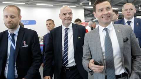 Surrounded by officials FIFA President Gianni Infantino, third from left, seen during his visit to Media centre prior the Group A soccer match between Portugal and Mexico, at the Kazan Arena, Russia, Sunday, June 18, 2017. (AP Photo/Sergei Grits)