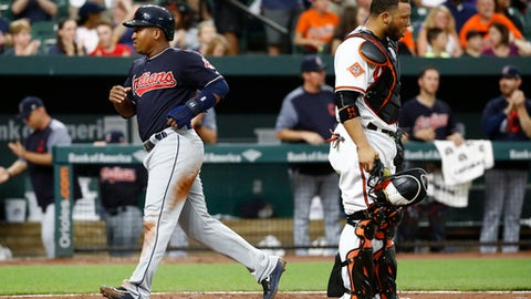 Cleveland Indians' Jose Ramirez, left, jogs past Baltimore Orioles catcher Welington Castillo for a run on a double by Edwin Encarnacion in the fourth inning of a baseball game in Baltimore, Monday, June 19, 2017. (AP Photo/Patrick Semansky)