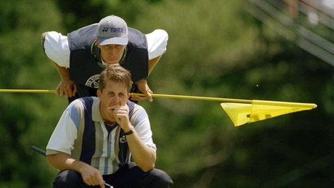 "FILE - In this June 16, 1995, file photo, Phil Mickelson stifles a yawn as he reads the green with his caddie Jim MacKay on the 15th green during the U.S. Open at Shinnecock Hills Golf Club in Southampton, N.Y. Mickelson and his caddie have decided to part ways after 25 years of one of the most famous player-caddie relationships on the PGA Tour. Mickelson and Jim ""Bones"" Mackay say the decision to split was mutual and not based on an incident. (AP Photo/Kathy Willens, File)"