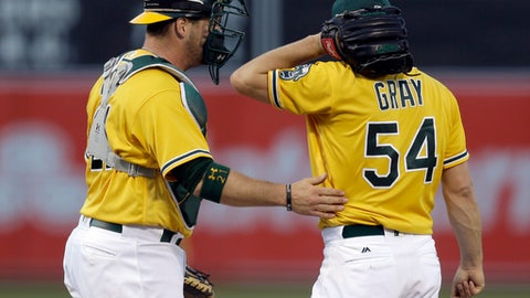 Oakland Athletics catcher Stephen Vogt, left, speaks with pitcher Sonny Gray (54) during the first inning of a baseball game against the Houston Astros on Tuesday, June 20, 2017, in Oakland, Calif. (AP Photo/Ben Margot)