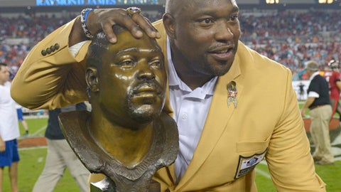 Former Tampa Bay Buccaneers player Warren Sapp smiles with a bust of himself after being inducted in the Ring of Honor ceremony during halftime in an NFL football game between the Tampa Bay Buccaneers and the Miami Dolphins in Tampa, Fla., Monday, Nov. 11, 2013.(AP Photo/Phelan M. Ebenhack)