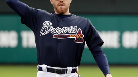 FILE - In this Tuesday, Feb. 21, 2017 file photo, Atlanta Braves first baseman Freddie Freeman warms up during a spring training baseball workout in Kissimmee, Fla. Freddie Freeman plans to move from first base to third base to keep Matt Adams' bat in the Braves' lineup. Freeman took grounders at third base before batting practice early Wednesday, June 21, 2017  and also made throws to first base.(AP Photo/John Raoux, File)