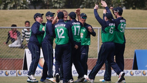 FILE - In this Friday, March 24, 2017 file photo, Ireland players celebrate the dismissal of Afghanistan's Najeeb Tarakai during their fifth one day international cricket match in Greater Noida, India. The rise of Afghanistan and Ireland in the ranks of international cricket gathered pace on Thursday, June 22 when they were voted in as full ICC members, meaning they can play test matches against the world's elite countries. (AP Photo/Altaf Qadri, file)