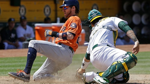 Houston Astros' Josh Reddick, left, slides to score behind Oakland Athletics catcher Bruce Maxwell during the eighth inning of a baseball game Thursday, June 22, 2017, in Oakland, Calif. (AP Photo/Ben Margot)