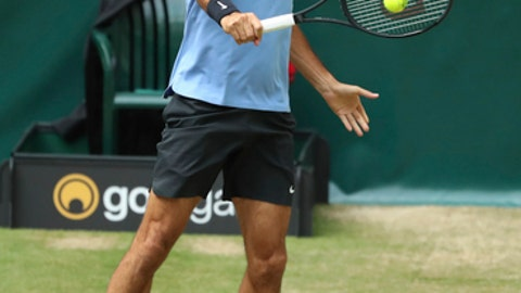 Switzerland's Roger Federer hits a backhand to beat Germany's Florian Mayer in the quarterfinal of the ATP tournament in Halle, Germany, Friday, June 23, 2017. (Friso Gentsch/dpa via AP)